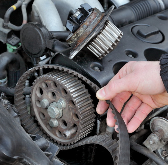 Car mechanic replacing timing belt at camshaft of modern engine